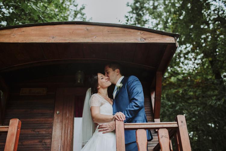 Mariés qui s'embrassent devant une roulotte